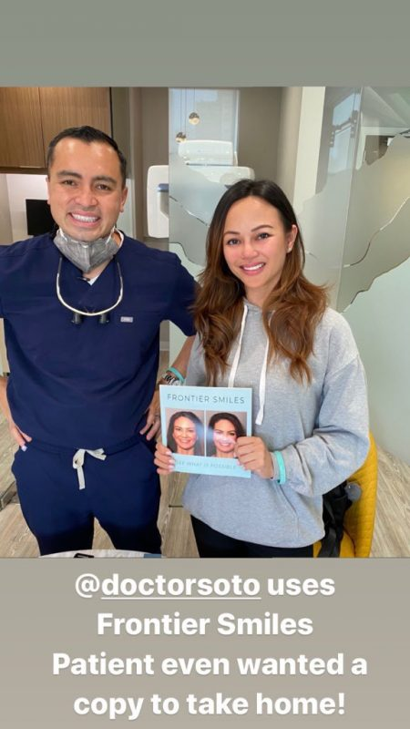 doctor robert soto with a patient holding the frontier smiles book